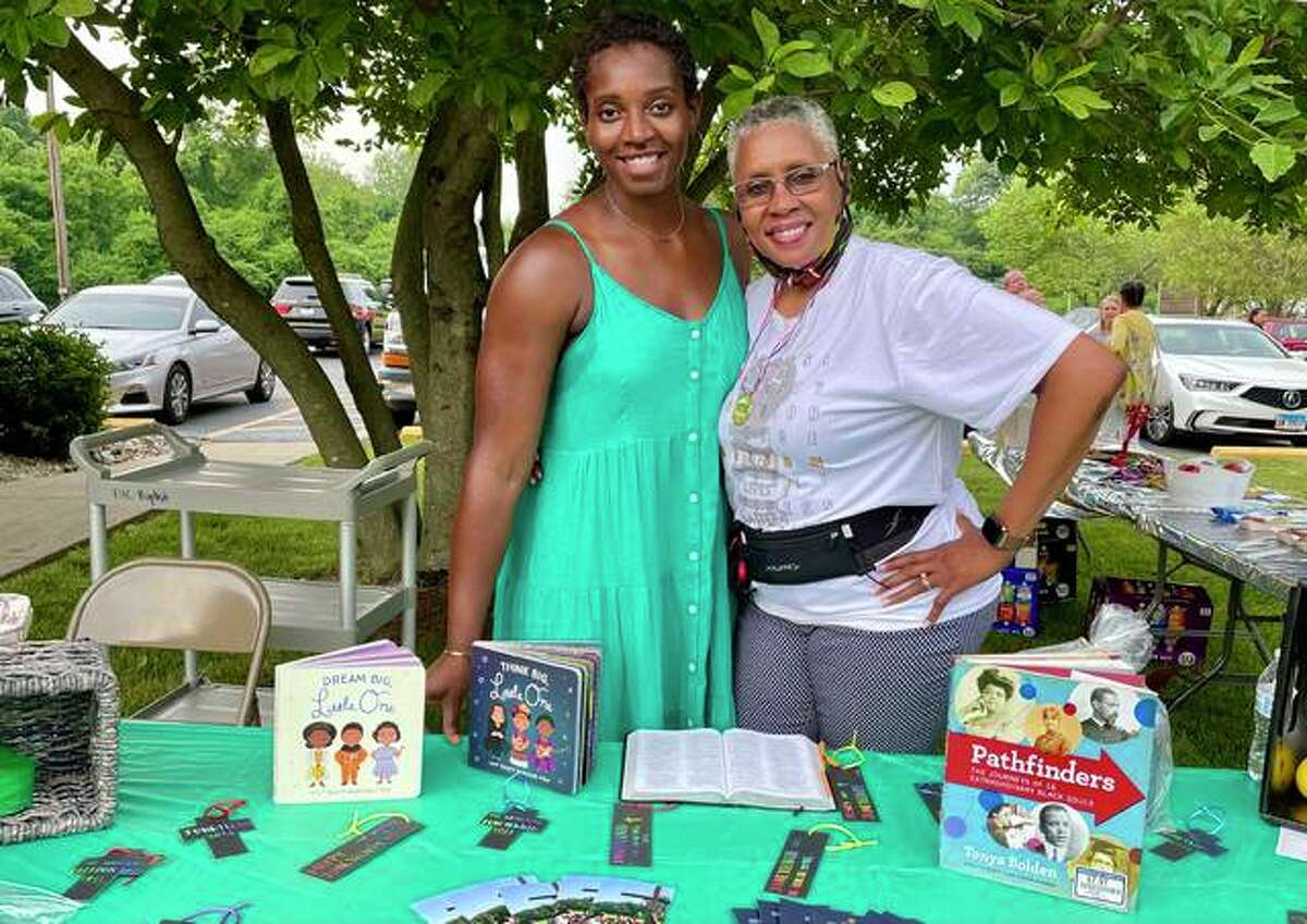 Event organizer Anya Covington, left, and Linda Jackson stand at the resources table for The Gathering's Juneteenth celebration at Esic Church.