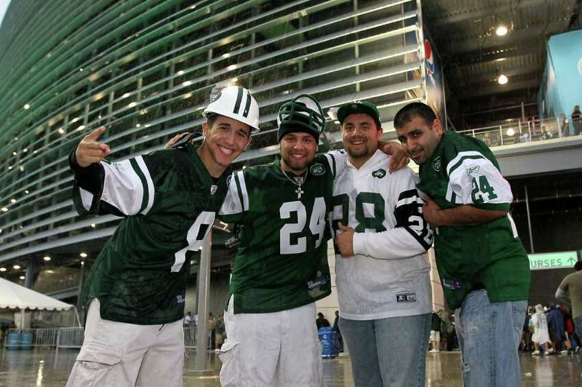 EAST RUTHERFORD, NJ - SEPTEMBER 13: Jets fans stand outside the stadium as rain falls prior to the New York Jets playing the Baltimore Ravens in their home opener at the New Meadowlands Stadium on September 13, 2010 in East Rutherford, New Jersey. (Photo by Jim McIsaac/Getty Images)