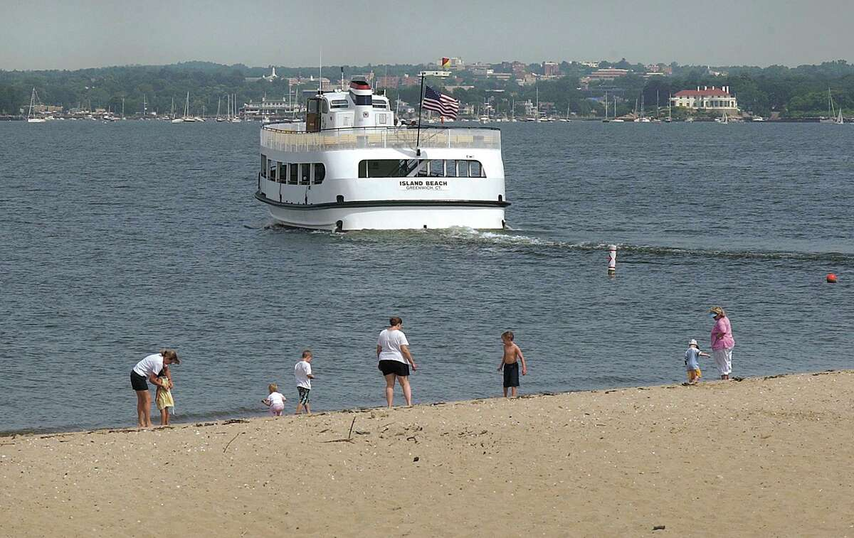 Visitors enjoy the shoreline of Island Beach as the Island Beach Ferry motors through Long Island Sound as it heads back to Greenwich Harbor after dropping off a ship-load of passengers in July 2002.