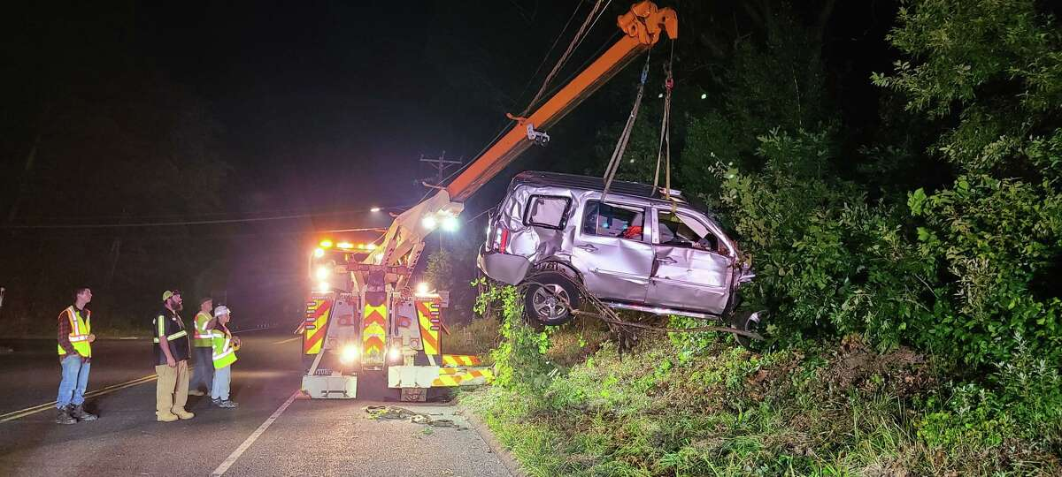 A crew removes the vehicle involved in rollover crash in Monroe, Conn., on Sunday, June 20, 2021, from the woods.
