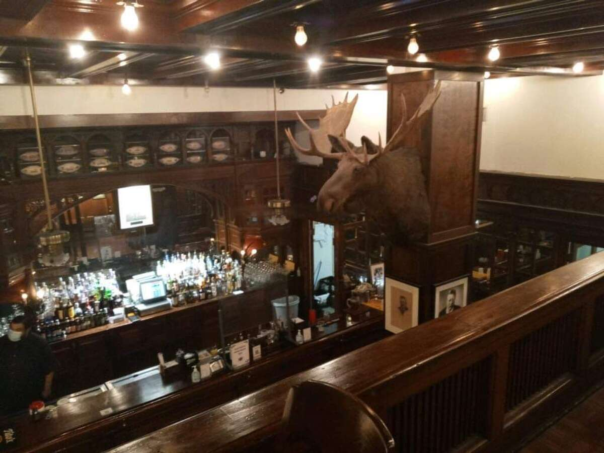 An unidentified figure appears in the mirror at the Menger Bar