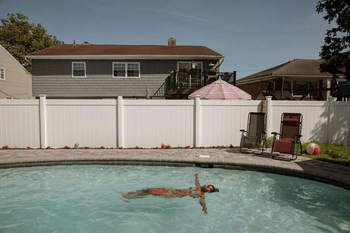 FILE -- A woman enjoys a swim in a backyard pool in Woodmere, N.Y., on July 15, 2020. A fire at a chemical plant and a pandemic-driven boom in the construction of backyard pools are the causes of a nationwide shortage of chlorine tablets and experts warn of a shortage that threatens to disrupt backyard plans from coast to coast.