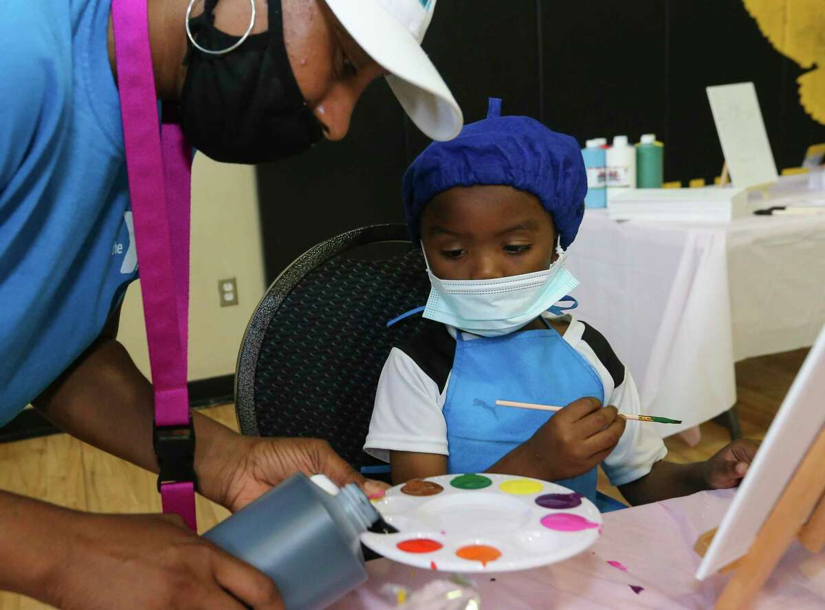 Youth Development Site Lead Shanae Scott pours paint for James Eastwood, 5, for a painting activity at day camp Friday, June 11, 2021, at Alief Family YMCA in Houston.