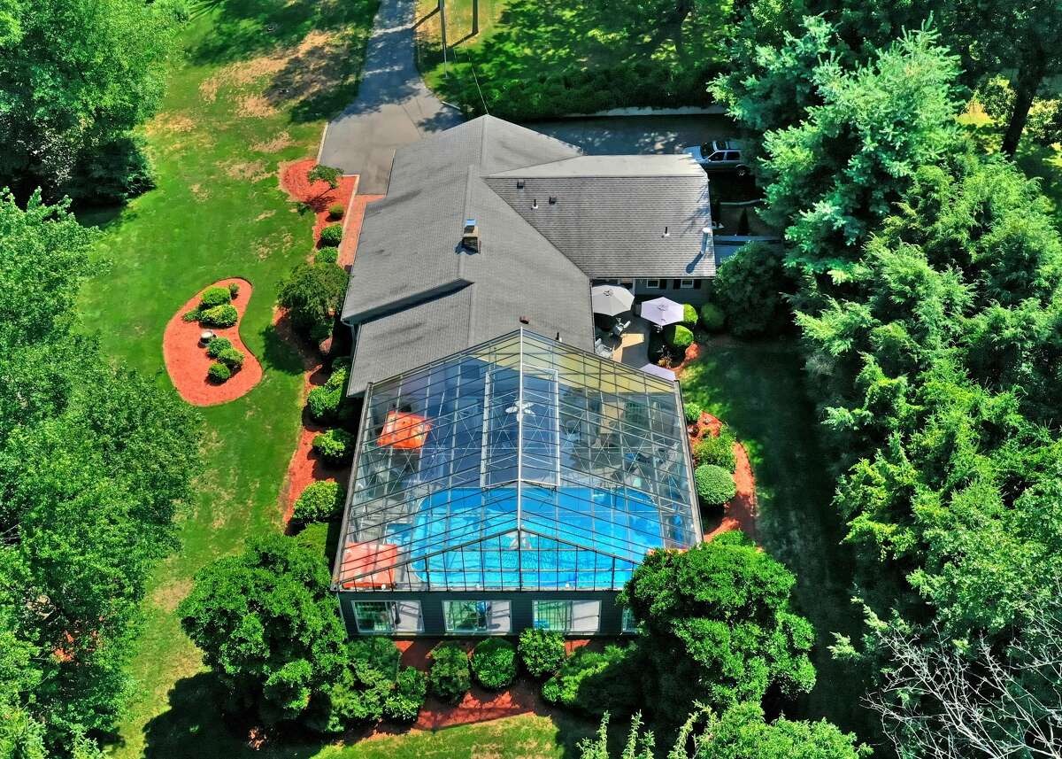 The home at 229 Cedarhurst Lane in Milford has a glass-enclosed in-ground pool.