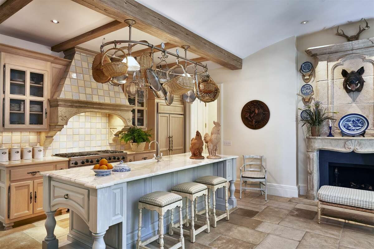 The kitchen in the home on 32 Doane Road in Deep River, Conn. has a large center island and a stone fireplace.