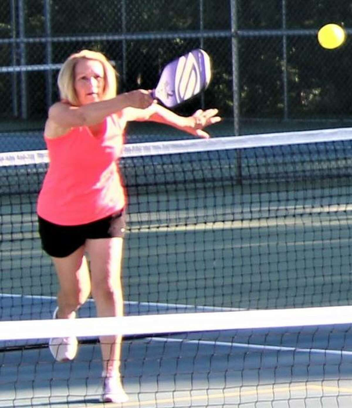 Joan Martin returns a volley during a June 16 pickleball game at Lewis and Clark Community College. Games are held on two of the unlighted tennis courts at the Simpson Tennis Complex.