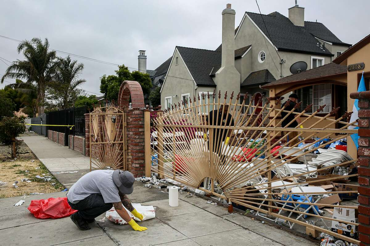 A crime scene restoration crew member cleans blood off the sidewalk after the mass shooting at a Richmond house party.