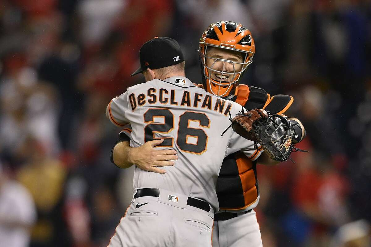 San Francisco Giants starting pitcher Anthony DeSclafani (26) and catcher Buster Posey, right, celebrate after a baseball game against the Washington Nationals, Friday, June 11, 2021, in Washington. DeSclafani threw a two-hitter as the Giants won 1-0. (AP Photo/Nick Wass)