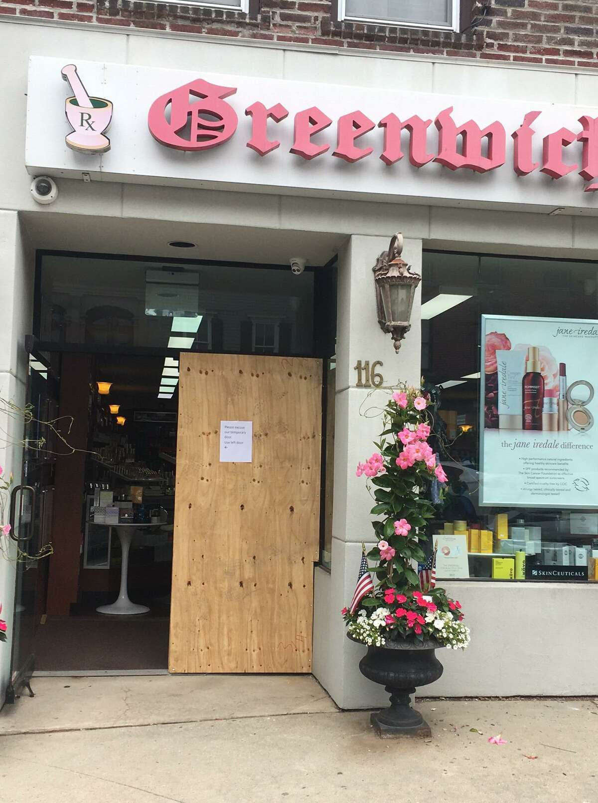 Plywood covered the damage left by intruders at two Greenwich Avenue pharmacies over the weekend.