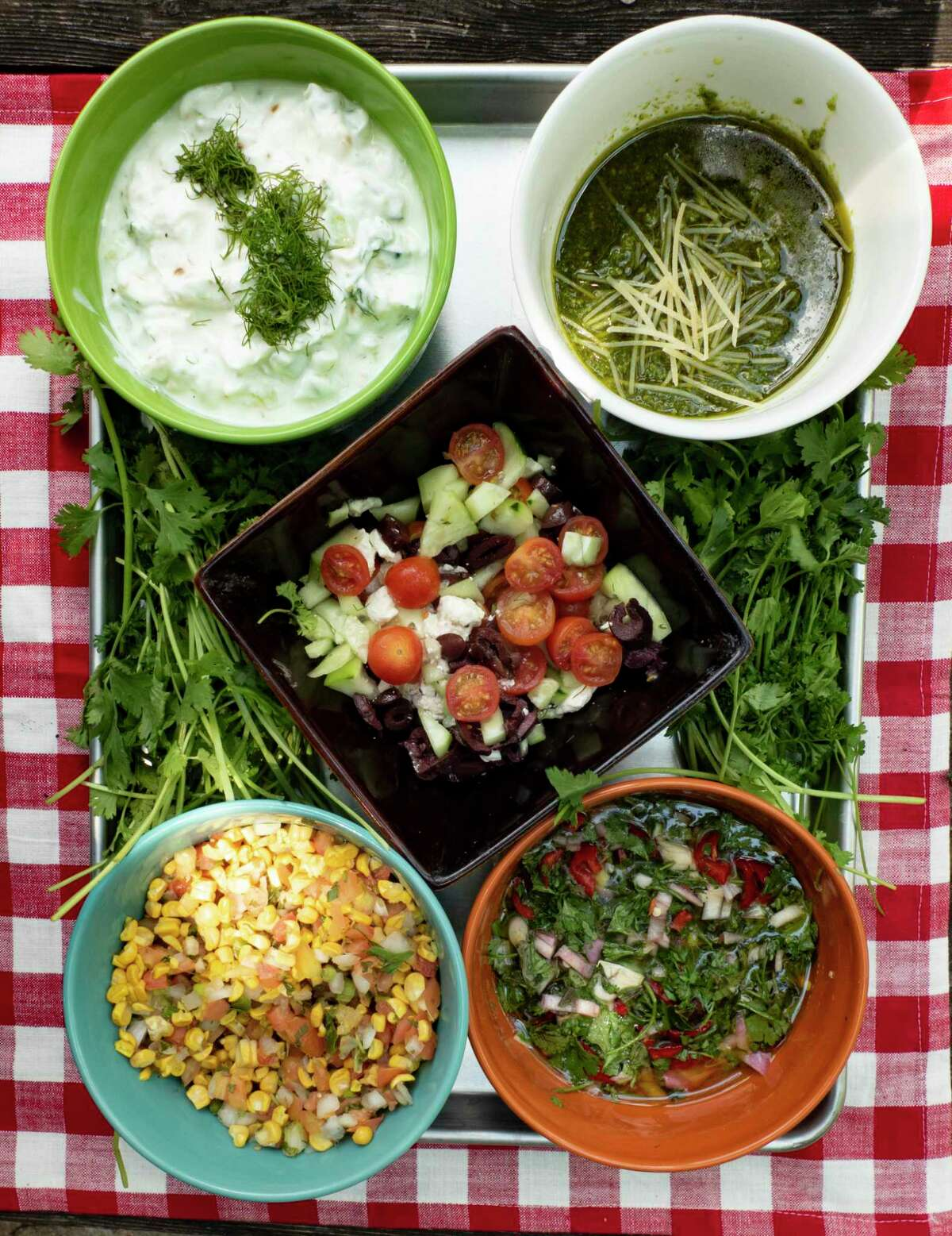 Toppings for hot dogs include (clockwise from top left): Tzatziki, pesto with Parmesan, chimichurri, pico de gallo with roasted corn and, in the middle, a Greek salad.