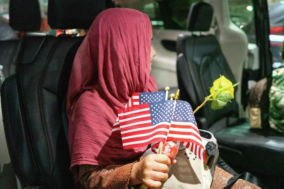 The family of an Afghan interpreter who was killed for working with the United States military arrives at George Bush Intercontinental Airport in Houston, June 12, 2021, greeted by volunteers with Combined Arms, a nonprofit serving veterans.