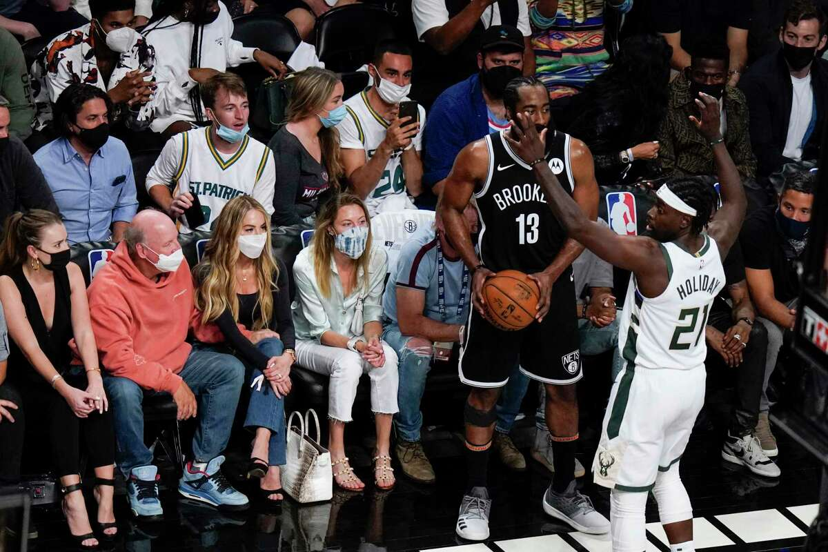 Fans watch as Milwaukee Bucks' Jrue Holiday (21) defends against Brooklyn Nets' James Harden (13) during the first half of Game 7 of a second-round NBA basketball playoff series Saturday, June 19, 2021, in New York.