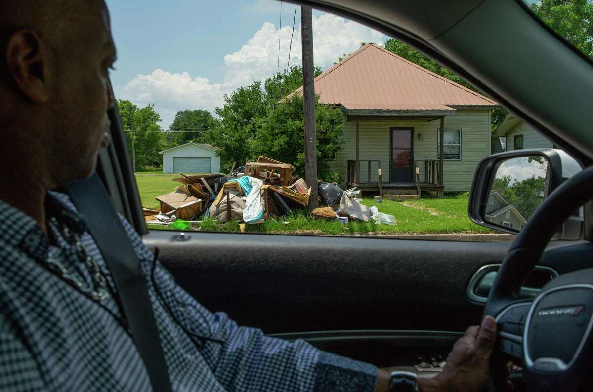 Port Arthur city employee Derrick Holland drives past a trash pile - which are common as people continue to deal with the aftermath of Hurricane Harvey and subsequent storms - on Tuesday, June 15, 2021, in Port Arthur.
