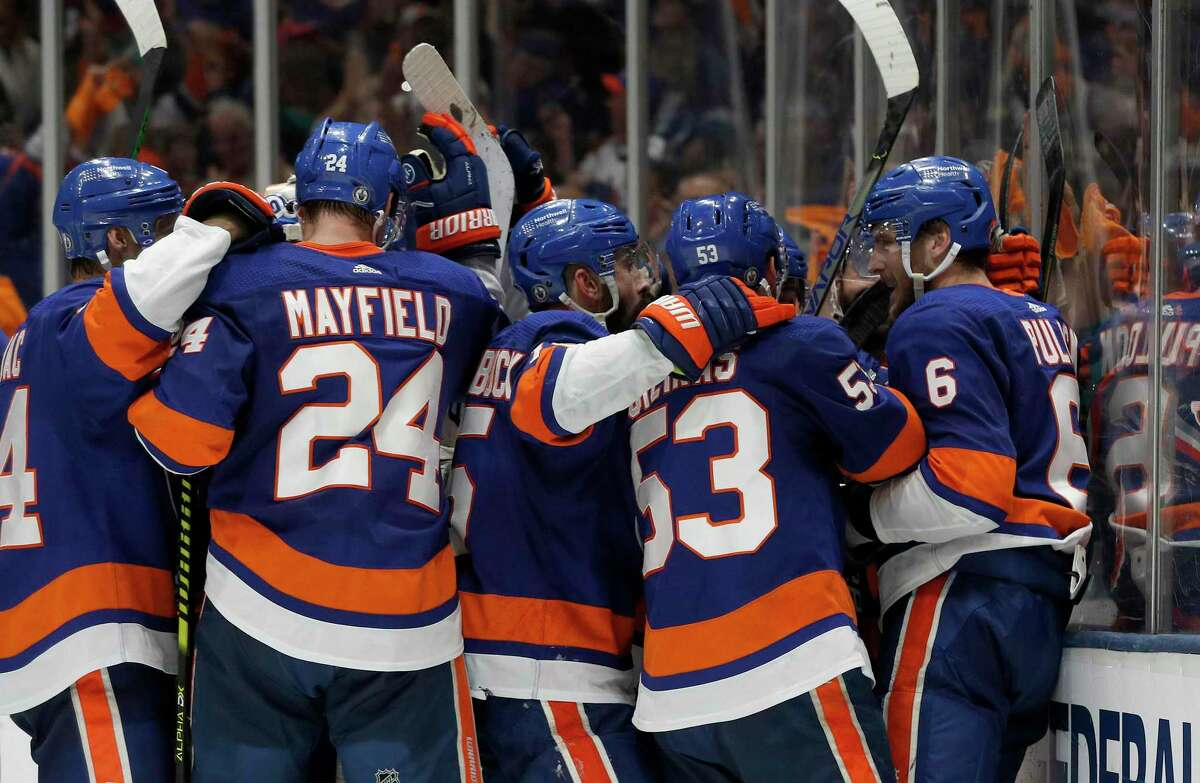 New York Islanders defenseman Ryan Pulock (6) and teammates celebrate a 3-2 win over the Tampa Bay Lightning in Game 4 of an NHL hockey Stanley Cup semifinal Saturday, June 19, 2021, in Uniondale, N.Y. (AP Photo/Jim McIsaac)