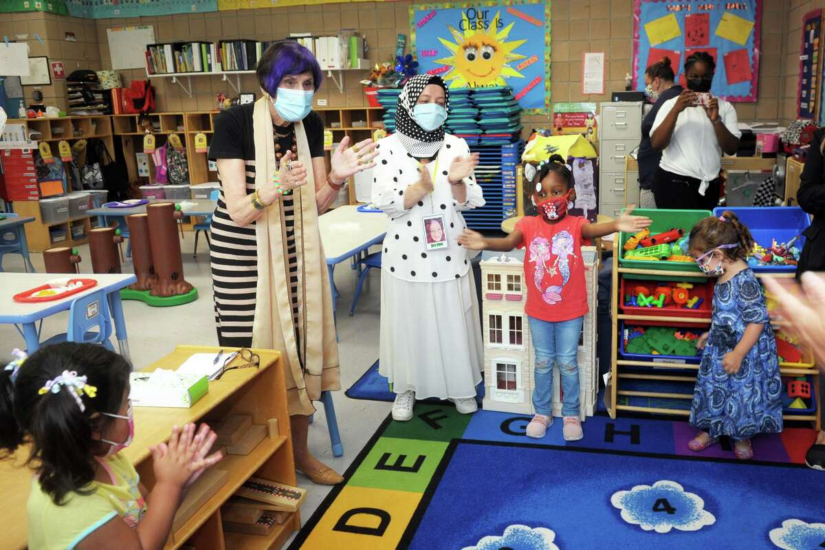U.S. Rep. Rosa DeLauro, left, claps along as students and their teachers sing for her in a classroom at TEAM's early education program in the Margaret Egan Center, in Milford, Conn. June 21, 2021. DeLauro spoke at the center to promote child tax credit awareness.