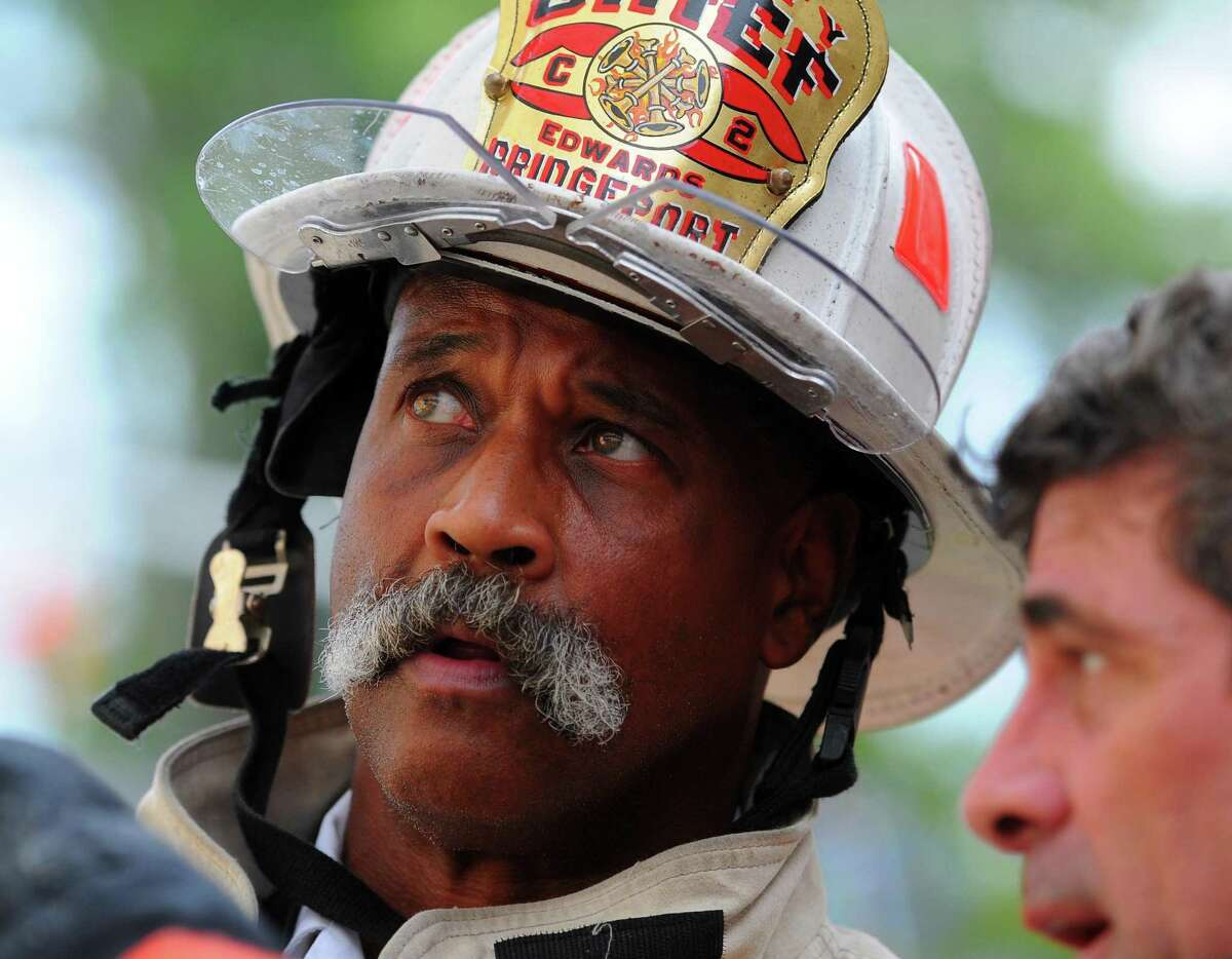 Bridgeport Deputy Fire Chief Lance Edwards surveys the scene at a two-alarm fire which ripped through a home at 1042 Iranistan Ave. in Bridgeport, Conn., on Wednesday, Aug. 21, 2019. Edwards was named to the top chief job on Monday.