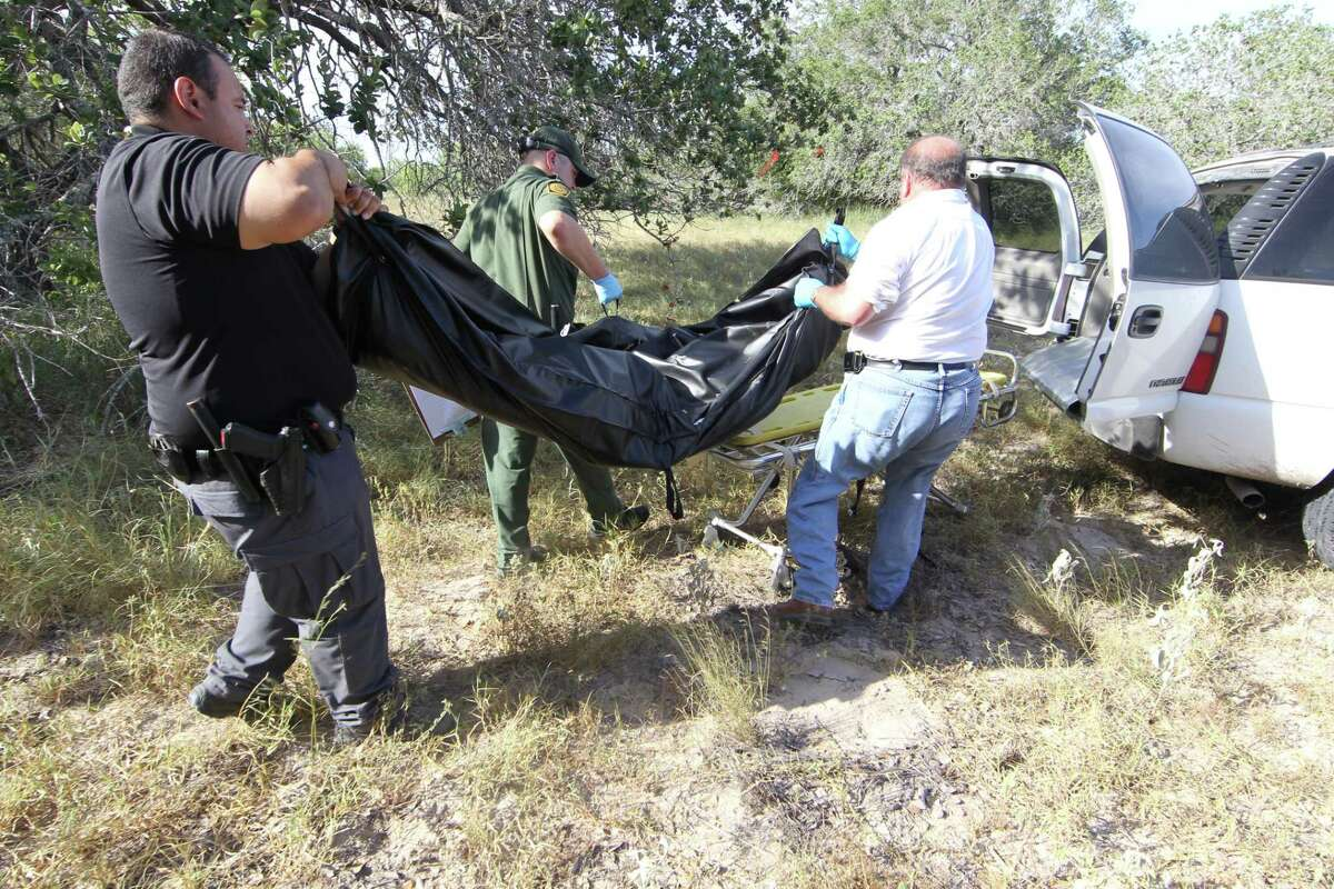 In this file photo, officials recover a jaw bone, dentures, skull and bible from a body in Brooks County in 2013. A sharp increase in the number of people crossing the border through difficult terrain has officials and rights advocates worried this summer will be especially lethal for migrants.