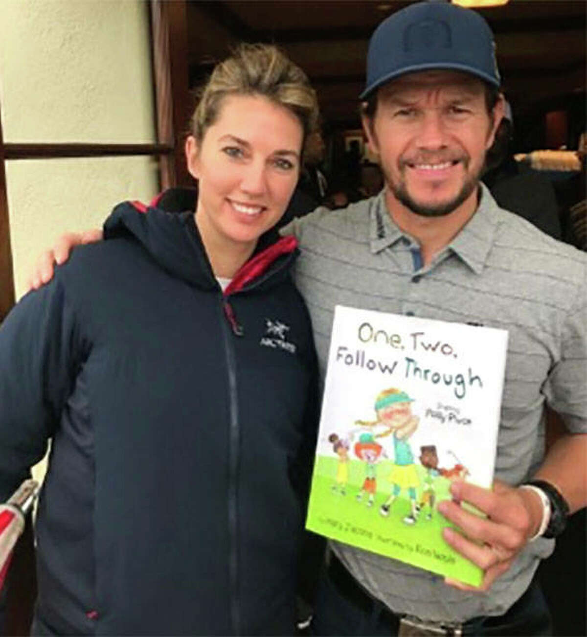 Mary Jacobs (left) poses with actor Mark Wahlberg, who is among the celebrities endorsing Jacobs' new children's book 'One, Two, Follow Through'. Jacobs, a girls golf state champion at Marquette Catholic in 2002, is the golf pro at Wilshire Country Club in Los Angeles and a new author.