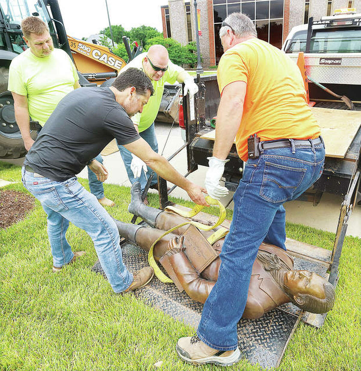 Edwardsville Public Works employees set the controversial statue of Ninian Edwards on the back of the lift gate used to put the statue in the back of a city truck. The founder of Edwardsville and first territorial governor in the early 1800s owned slaves. After a cement pad is finished, the statue will be returned to City Plaza in a slightly different spot.