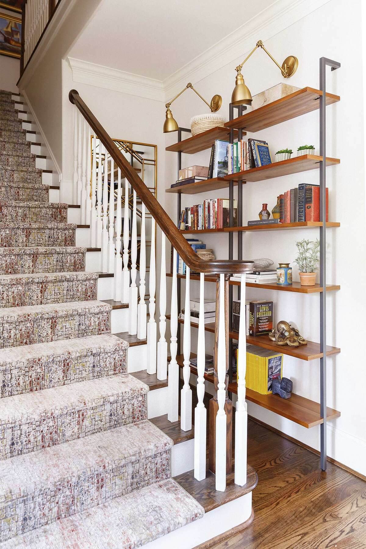 A narrow dead-end alongside a staircase was used for a stack of shelves that displayed a family's books and mementos.