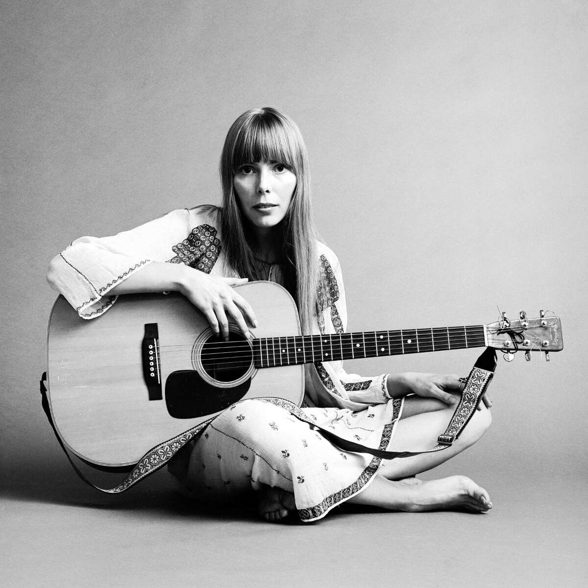 20th November 1968: Portrait of American musician Joni Mitchell seated on the floor with her acoustic guitar in her lap. This image was from a shoot for the fashion magazine Vogue. Mitchell wears a white cotton dress.
