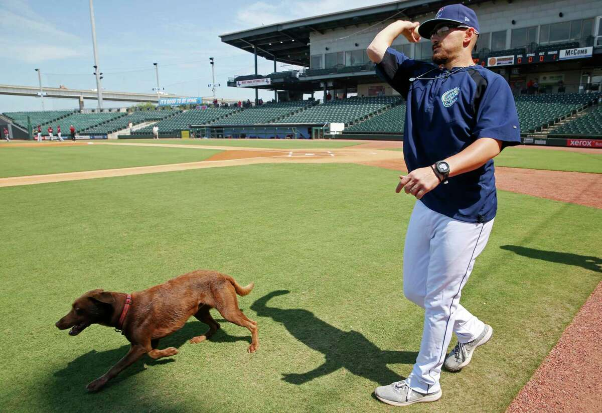 Corpus Christi Hooks pitcher J.P. France plays fetch with Teal before the start of a recent doubleheader at Whataburger Field.