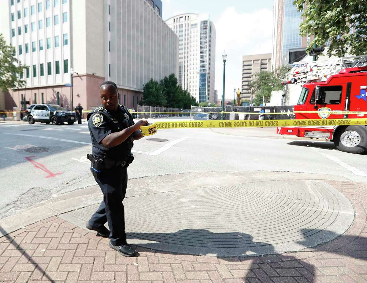 A Harris County Precinct 1 Sheriffs Deputy puts up crime scene tape across the street as Houston firefighters and investigators were on the scene at Preston and Caroline, after construction workers located, what they believe to be a cannonball or other potential explosive device, Thursday, June 17, 2021.