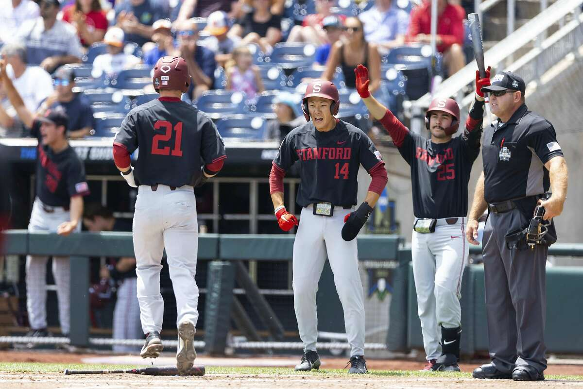 Stanford's Tim Tawa (21) and Eddie Park (14) celebrate after scoring on Brock Jones' double during a seven-run third inning against Arizona in a College World Series game in Omaha, Neb.
