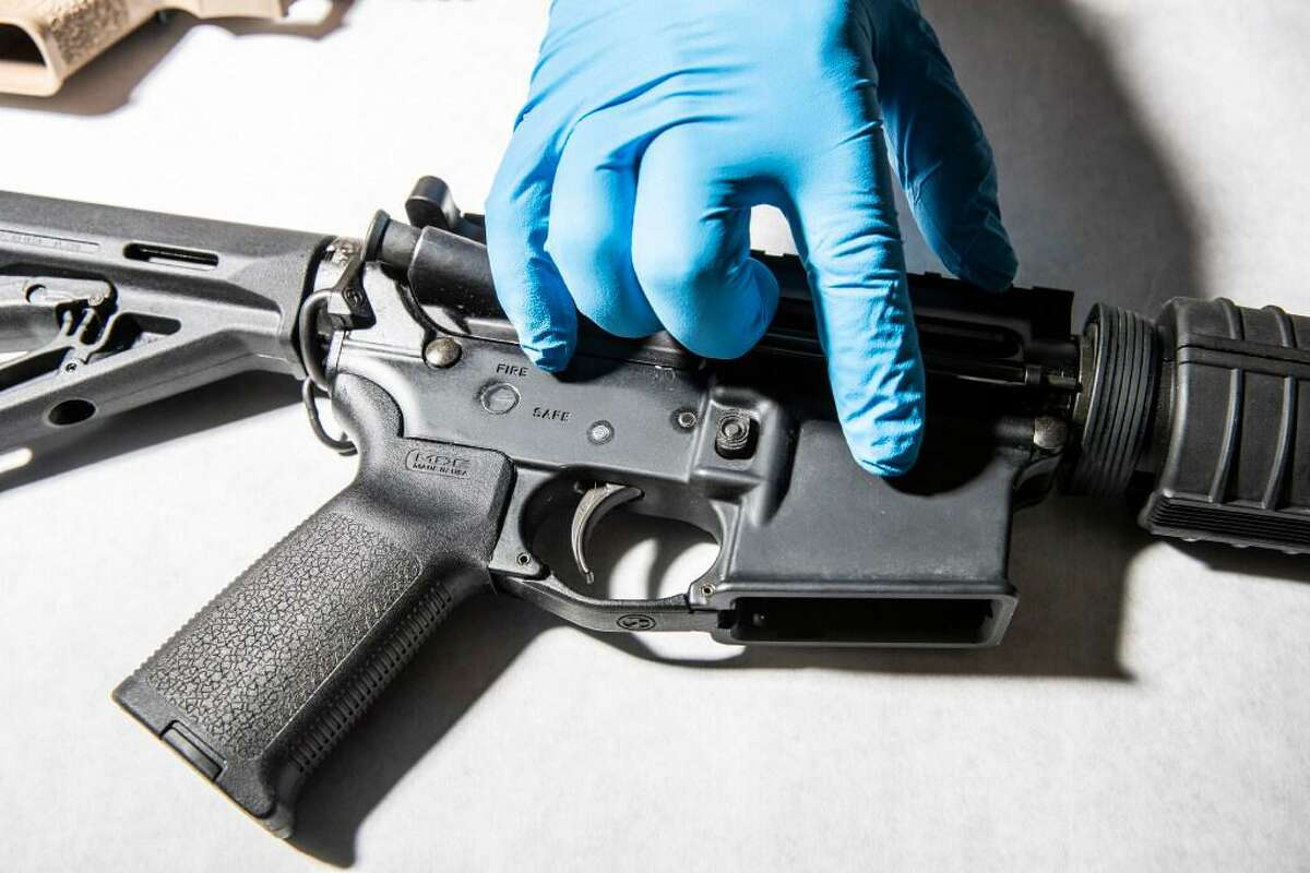 A police service technician with the Oakland Police Department Property and Evidence Unit points to a seized AR-15 assault rifle from a sample of ghost guns, or unregistered and untraceable firearms, at the department's headquarters in Oakland, April 15, 2021.