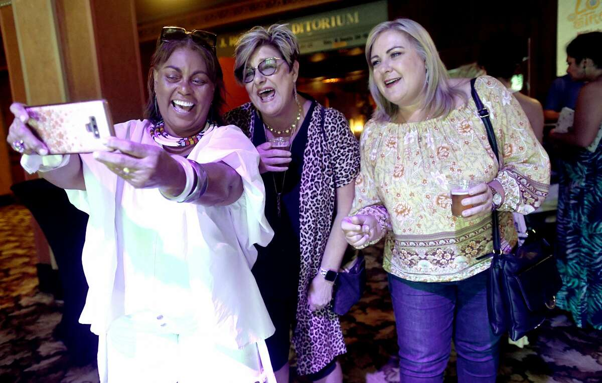 From left, Ava Graves, Teri Wallace and Terri Lewis record their impromptu karaoke to music playing overhead as they await the start of Ole Lonesome's performance onstage at the Jefferson Theatre on Beaumont's Make Music Day Monday. Photo made Monday, June 21, 2021 Kim Brent/The Enterprise