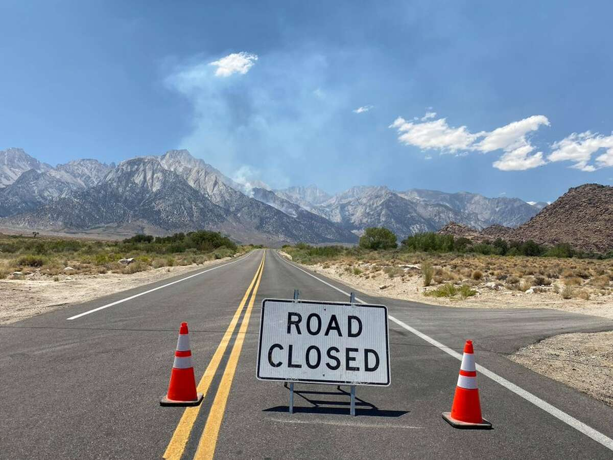 A road closure sign with smoke from the Inyo Creek Fire in the background. Courtesy of the Inyo National Forest Twitter account.