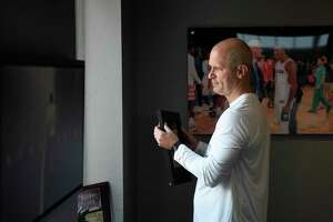 UConn men's basketball coach Dan Hurley takes a framed photo off the wall in his office before practice at the Werth Family UConn Basketball Champions Center on the UConn main campus in Storrs, Conn. Wednesday, June 9, 2021.