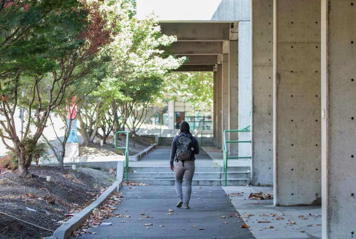 A student walks past leaves and trash on the west side of campus at Laney College. A new grand jury report found that the elected trustees running the East Bay's Peralta Community College District, including Laney College, have experienced great dysfunction.