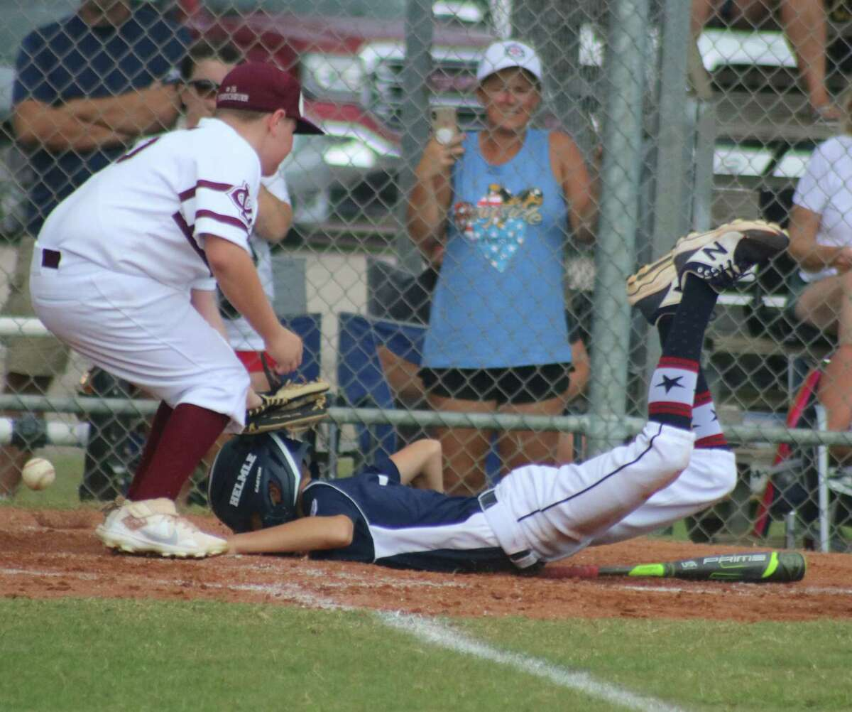 Bayside's Drew Helmle survived a third-inning rundown, landing on home plate with this belly landing. The baseball is skipping by the pitcher as he does so.