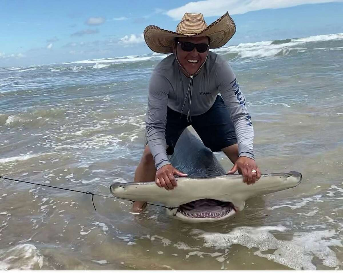 """Local Joe Guerrero, 38, reeled in a 12-foot hammerhead shark while fishing off the shore at Padre Island National Seashore on Saturday. He says he scored his """"dream"""" catch while with two of his children."""