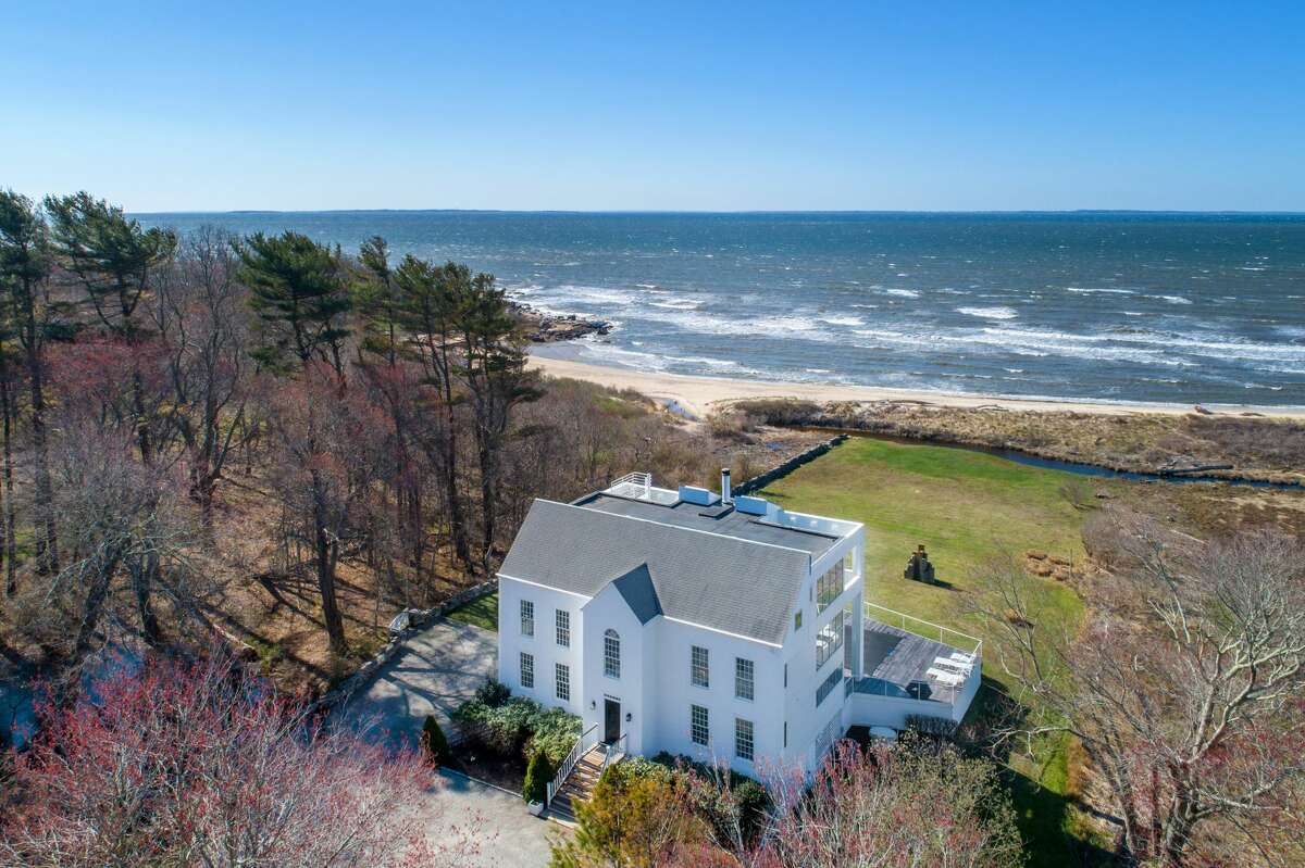 The home on 11 Dennis Road in Old Lyme, Conn. has a traditional Colonial façadefacing the street and a modern exterior facing the Long Island Sound.