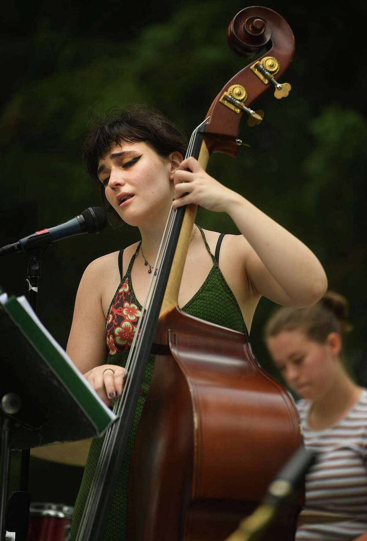 """Bassist Sarah Dimicelli, of Ridgefield, sings the classic """"Lullaby of Birdland"""" during a Make Music Day jazz performance by the Scott Robert Sextet at Ballard Park in Ridgefield, Conn. Monday, June 21, 2021."""