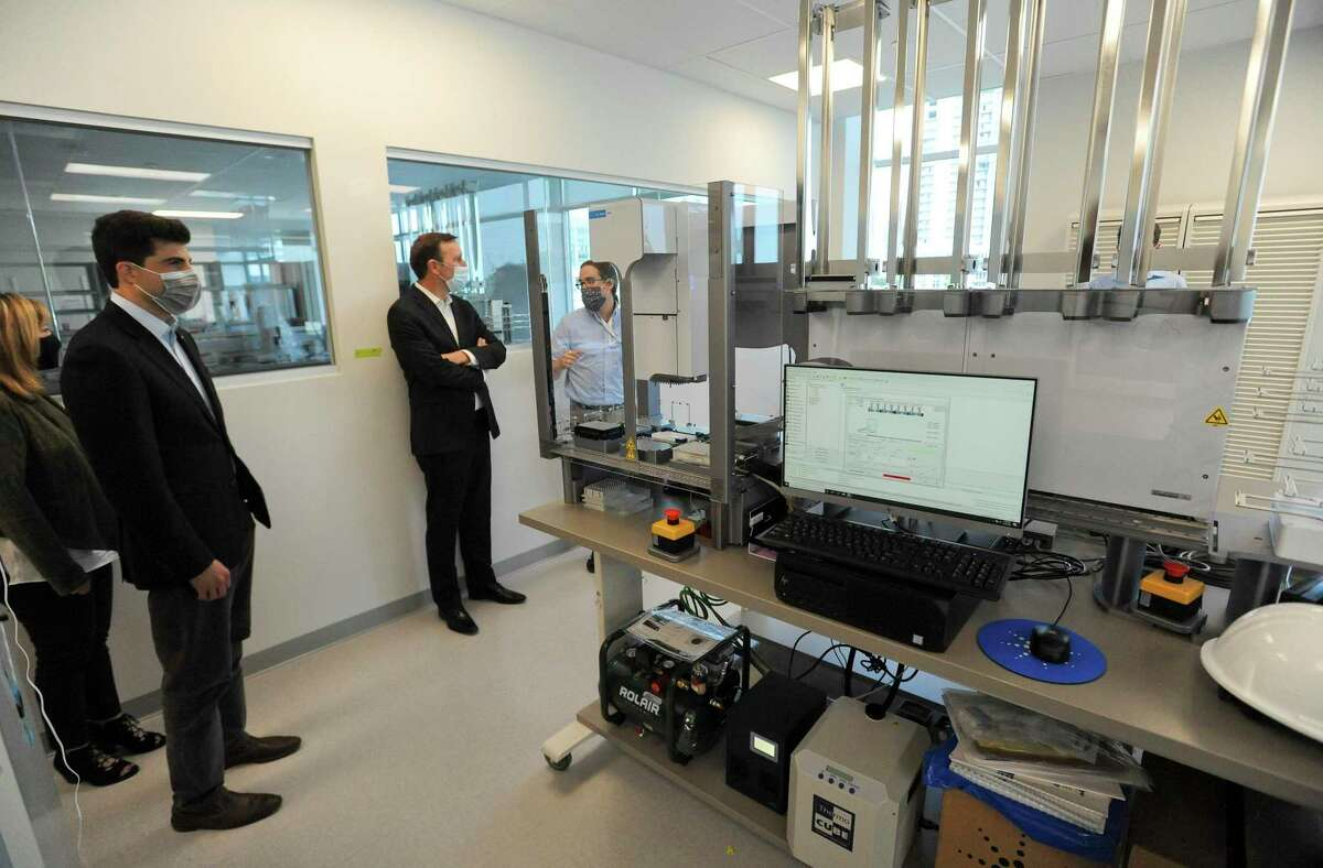 State Rep. Matt Blumenthal, second from left, and Sen. Chris Murphy, D-Connecticut, second from right, walk through a room during a tour of Sema4's lab at 62 Southfield Ave., in Stamford, Conn., on Sept. 18, 2020.