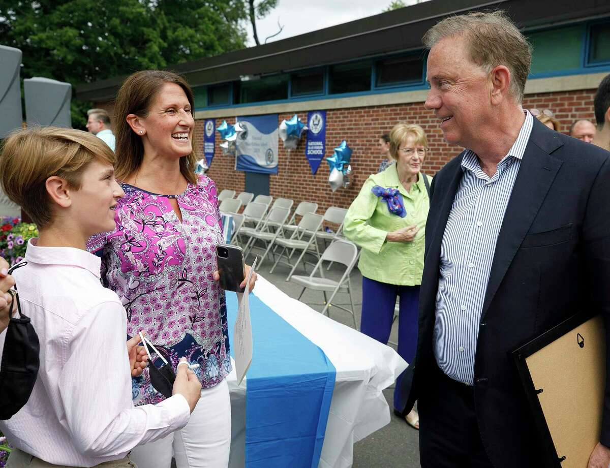 Gov. Ned Lamont in mid-June 2021 in Cheshire, Conn., speaking with sixth-grade student Grant Paul and his mother Nicole. On June 22, the Connecticut Department of Labor noted a boost in education hiring which DOL indicated could be the result of schools increasing their summer programming ahead of the coming academic year. (Dave Zajac/Record-Journal via AP)