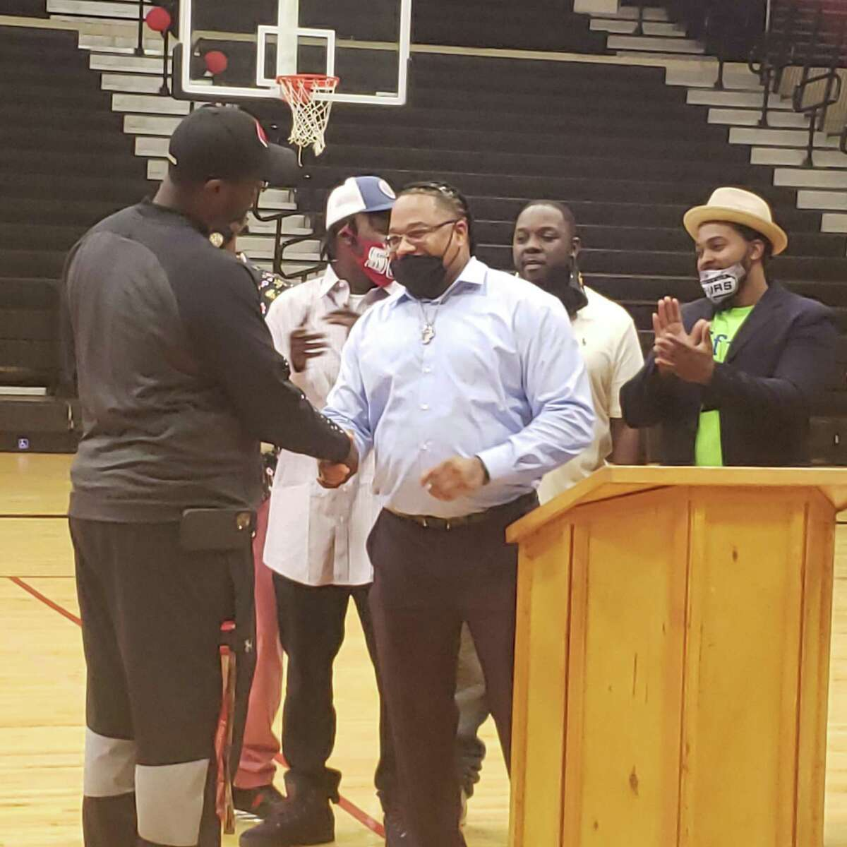 Milas Williams, from the GOOD Commission, presents a $1,700 check to coach Rodney Clark to help his basketball team attend the Texas Association of Basketball Coaches Boys Showcase from June 25 to June 27.