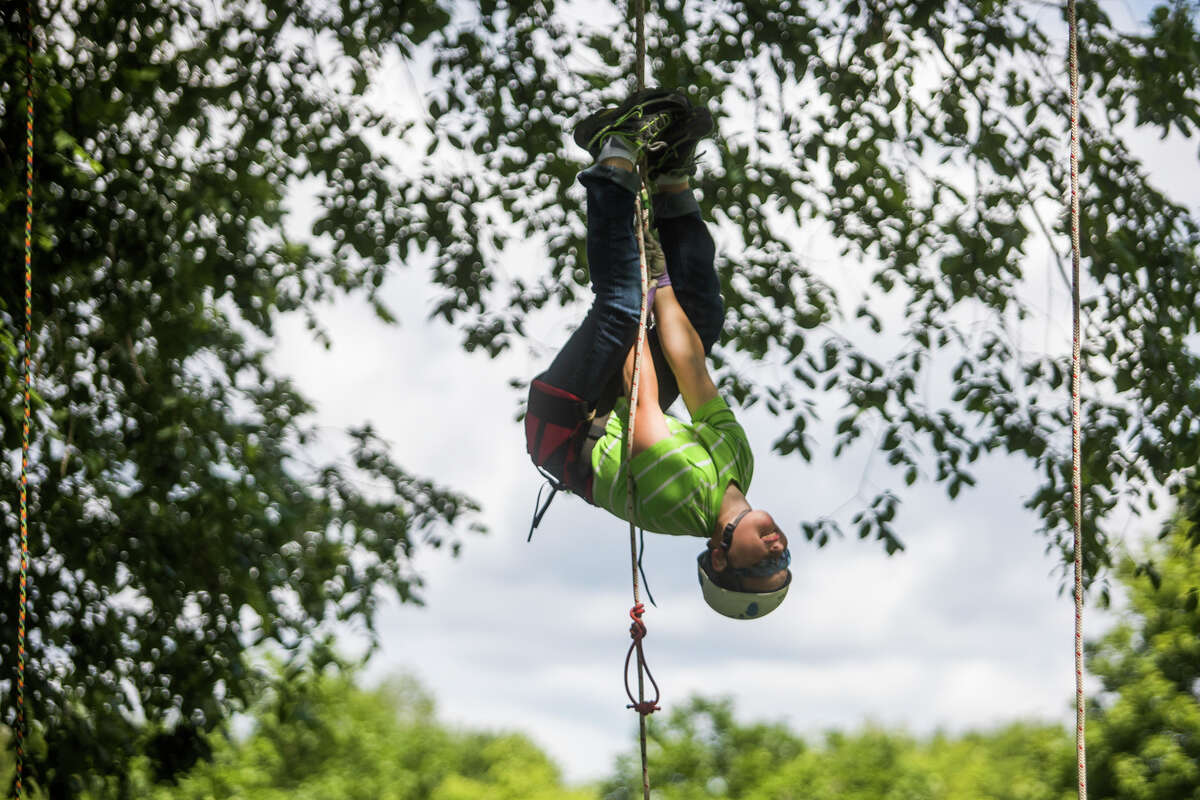 Henry Vanchura, 10, hangs upside down while participating in a tree climbing event hosted by arborists at Dow Gardens Tuesday, June 22, 2021 in Midland. (Katy Kildee/kkildee@mdn.net)