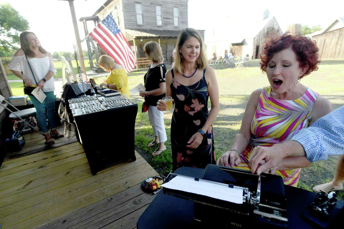 Lori Wenner reacts as she gets an old school typing lesson as she and friends, including Rebecca Boone, take in Andrea Beck's typewriter jewelry booth while attending wine and jazz night at the Spindletop-Gladys City Boomtown Museum Friday. Photo made Friday, June 18, 2021 Kim Brent/The Enterprise