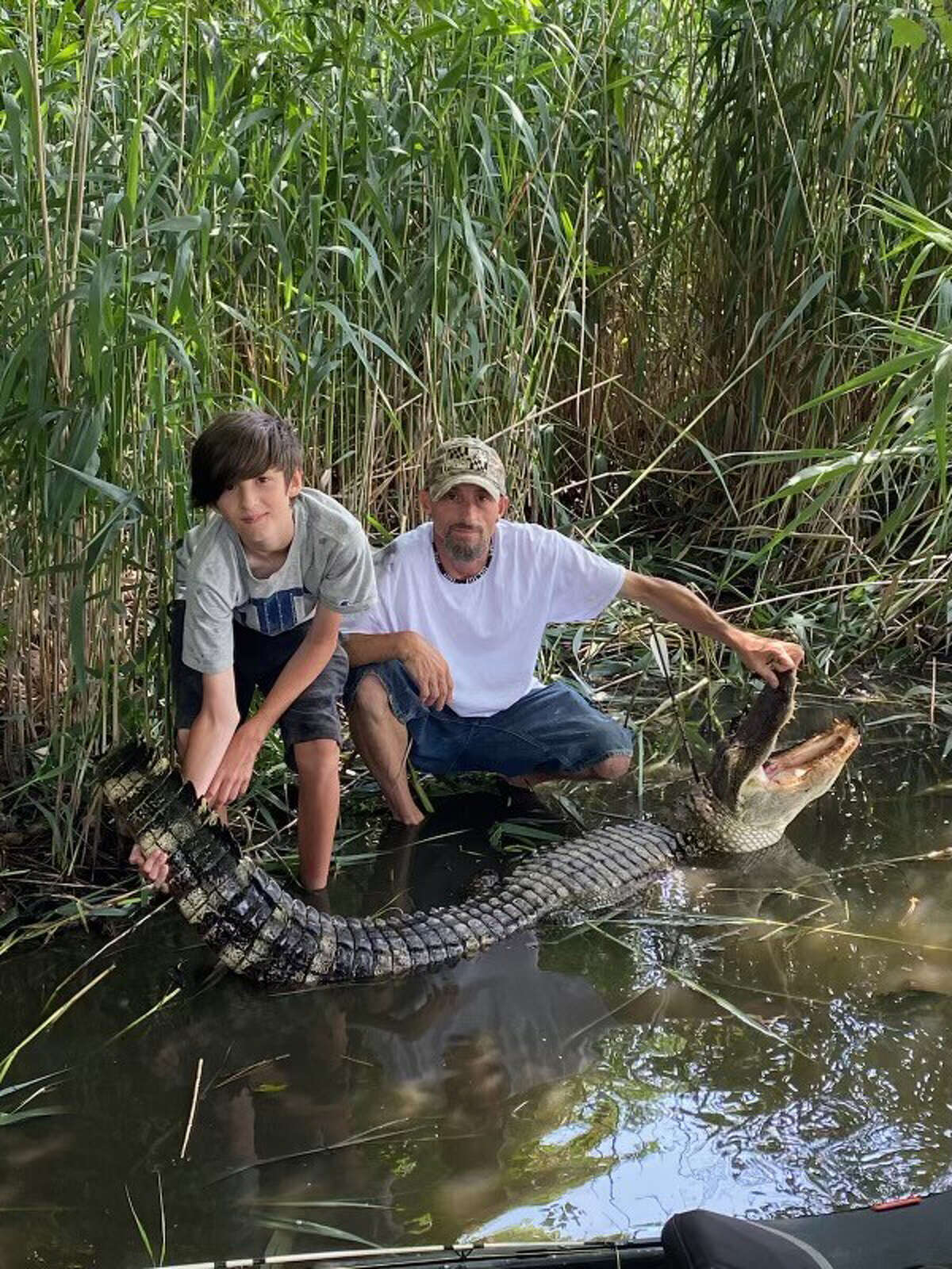 William Adams, right, of Lusby, Md., is shown with his son, Jake, as the pair hold an almost 8-foot-long alligator they found in a pond near their home off the Chesapeake Bay in Southern Maryland.