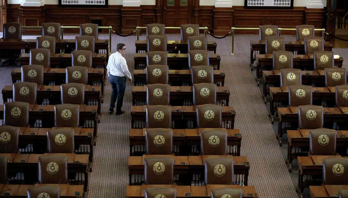 """Chris Currens, who works in the office of the sergeant-at-arms in the Texas House, walks through an empty chamber, Wednesday, Aug. 16, 2017, in Austin, Texas. The Texas Legislature adjourned Tuesday and a Texas """"bathroom bill"""" targeting transgender people died again along with many of Republican Gov. Greg Abbott's summer demands. (AP Photo/Eric Gay)"""