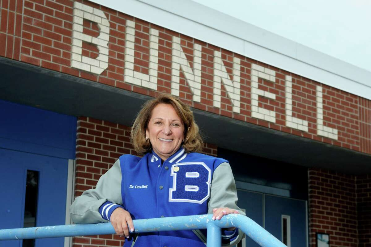 Principal Nancy Dowling poses in front of Frank Scott Bunnell High School, in Stratford, Conn. June 22, 2021. Dowling is retiring this month after a 37-year career as a teacher and school administrator.