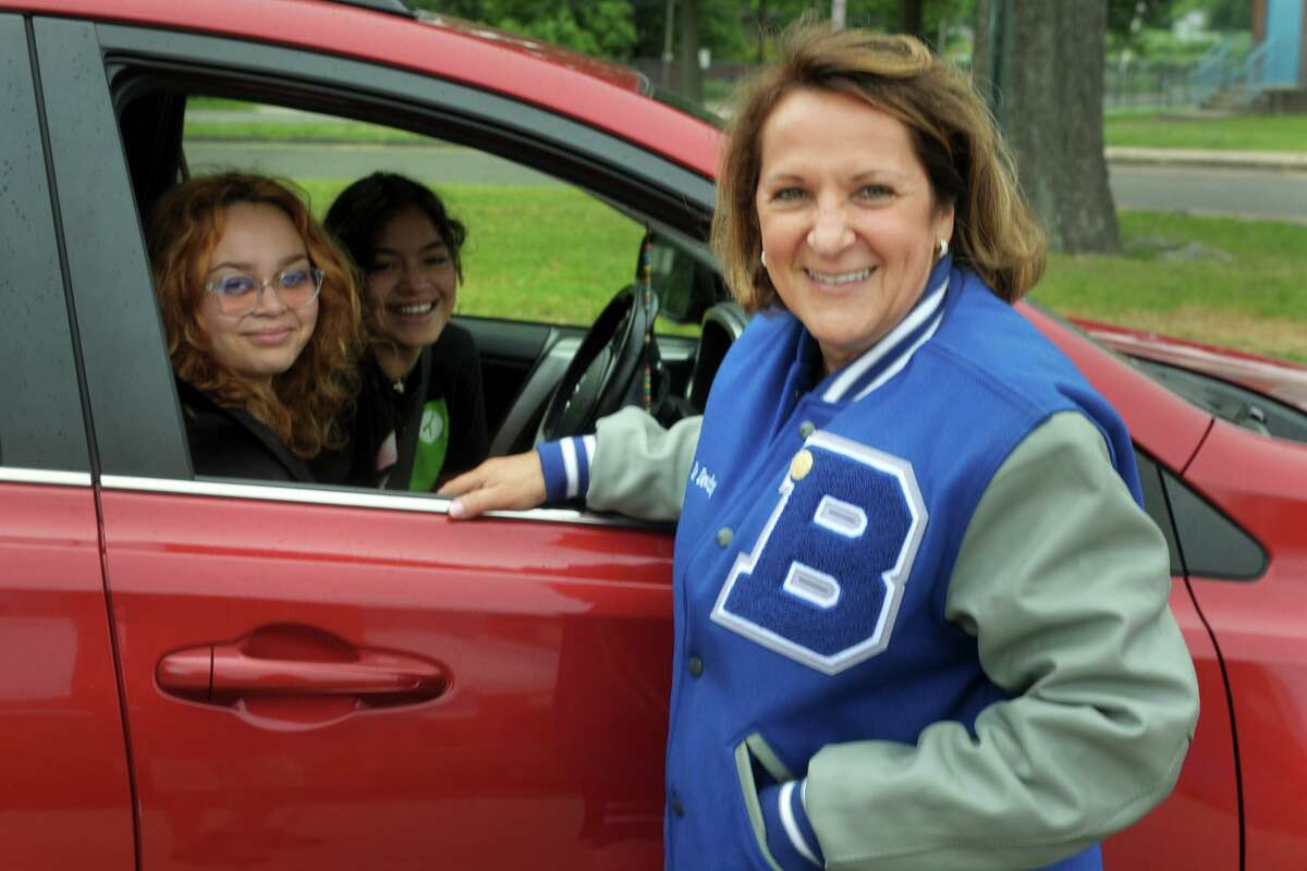 Principal Nancy Dowling talks with two recent graduates, Bailey Mitchell-Warren and Rosemery Nieto, in front of Frank Scott Bunnell High School, in Stratford, Conn. June 22, 2021. Dowling is retiring this month after a 37-year career as a teacher and school administrator.