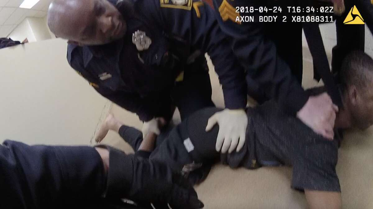 Milford Officer Erek Robinson holds a man to the ground inside a police station after putting the man into a chokehold that internal investigators later determined was improper.