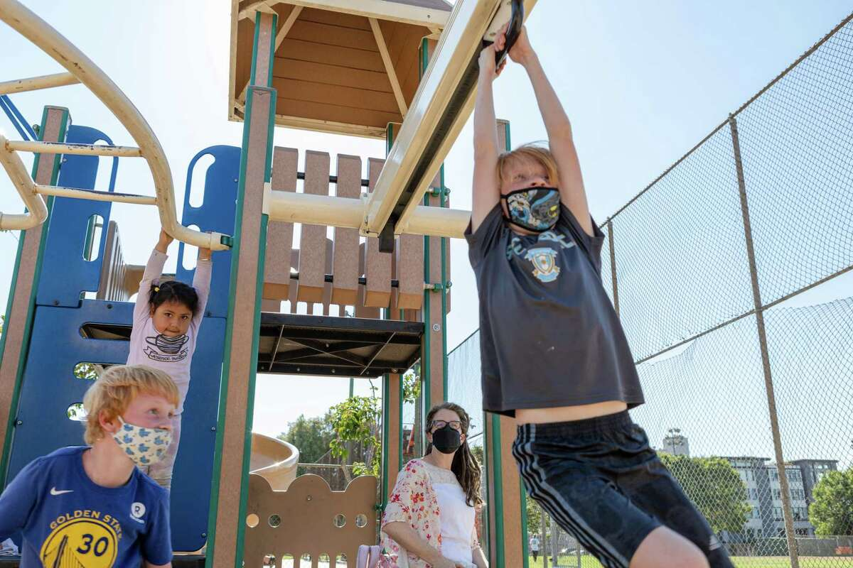 Ellis Barringhaus (left) and companions enjoy the playground at Jackson Park in San Francisco. Cases of COVID-19 among children have risen in S.F. and across California in recent weeks.