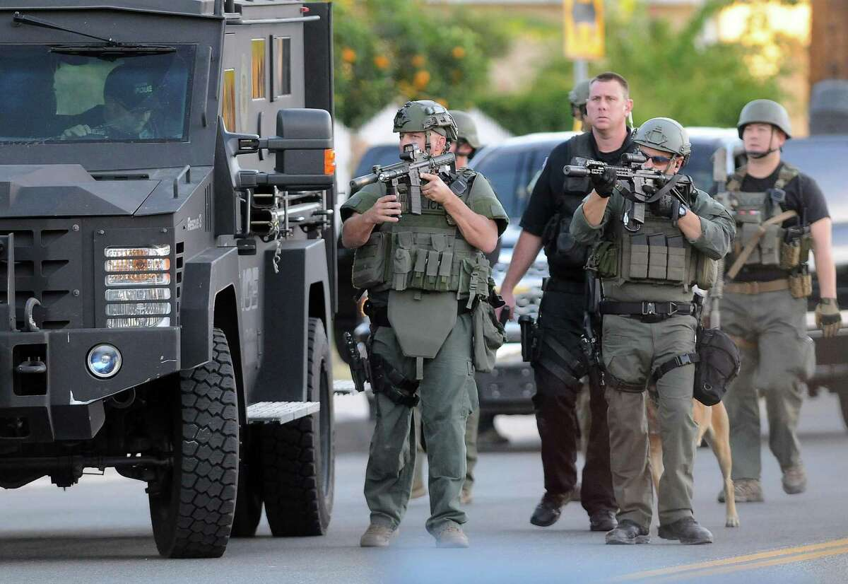 Authorities search an area following a shooting that killed 14 people at a social services center in San Bernardino on Dec. 2, 2015. A suit was filed by relatives of three of the people killed when a husband and wife entered a regional social services center during a holiday party.
