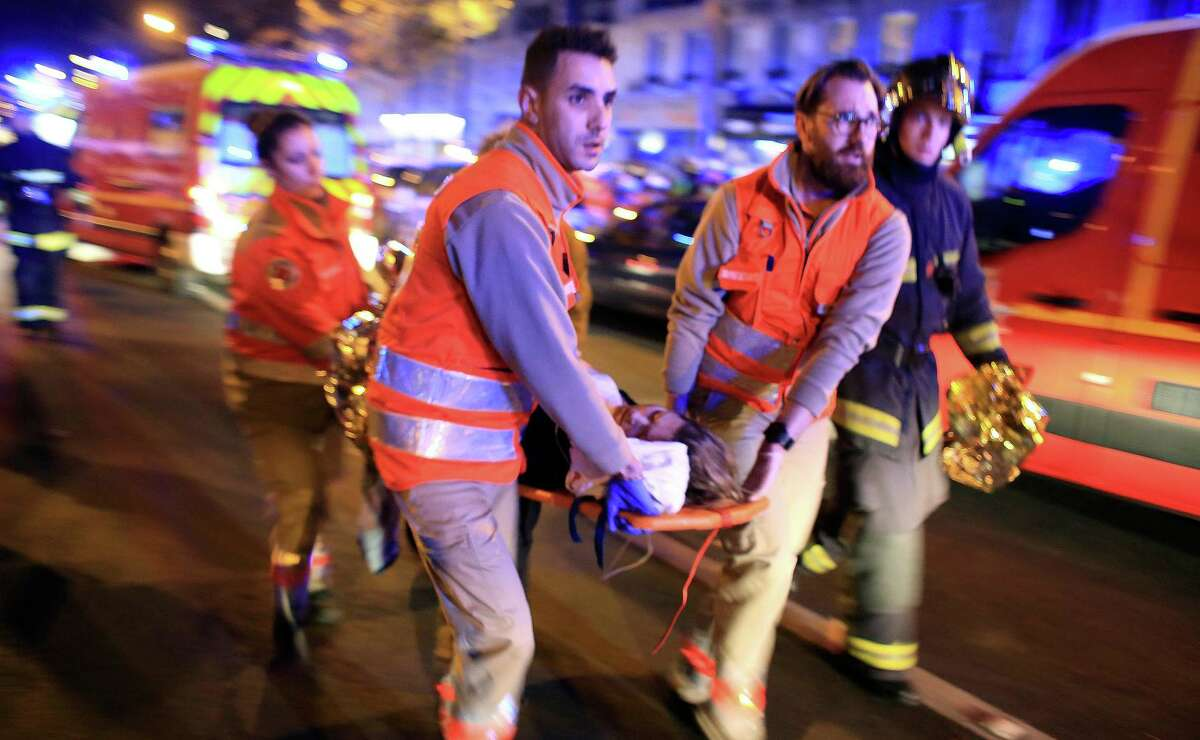 A woman is evacuated from the Bataclan concert hall after the mass shootings in Paris on Nov. 13, 2015. A U.S. lawsuit against internet companies over the Paris shootings was filed by a California relative of a U.S. citizen killed by ISIS gunmen at a restaurant that day.